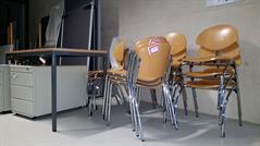 Gestapelte Stühle im Flur mit Betonwand