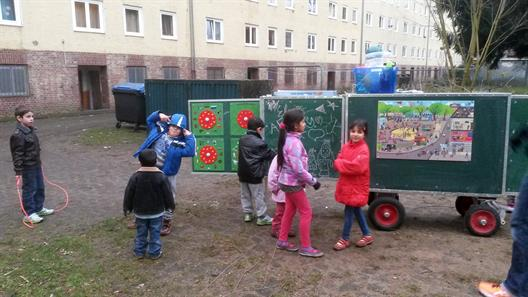 Children playing in front of the trailer of Mobile School