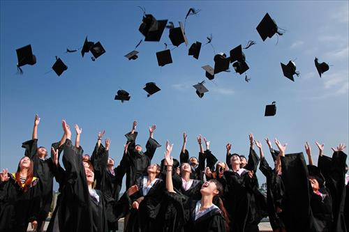 Graduates throw their hats in the blue sky