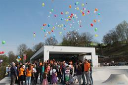 This picture shows a pavilion. In front of it thereÄs a crowd of adults and young people celebrating the openig ceremony of the youth pavilion. In the sky there are coloured balloons, attached to the are messages.