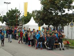 "On this picture there's a crowd of children waiting in front of the entrance of ""Mini-München"". In the backgrounds are some  tents."