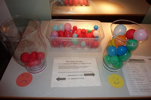 Colored balls in glasses on a withe Table and Smileys