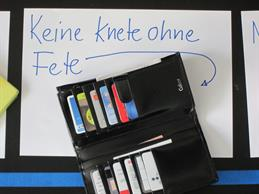 You can see an open wallet. In the background is geschreiben : No dough without party.