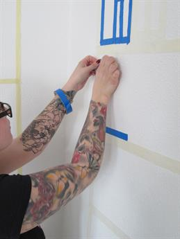 The photo shows a young woman who sticks with adhesive structures on a wall.