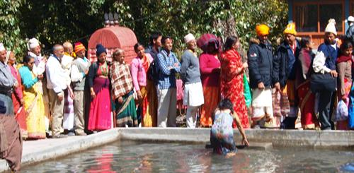People in the Himalayas, standing in a queue attending a ceremony with a woman in a water basin.