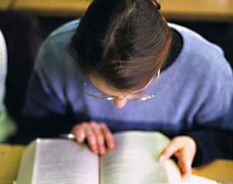 A female student is reading a book.