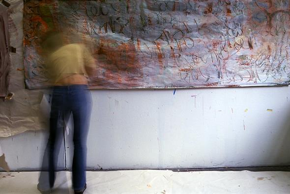 Fuzzy and moving person in front of a canvas with colored drawn letters.
