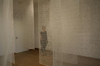 transparent material is hanging from the ceiling. On it is a text written with hand