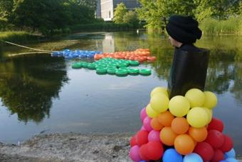A lake with coloured rubber rings. In foreground stands a person with a dress out of balloons