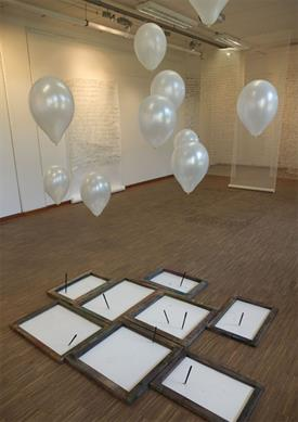 A room. You see white balloons full of helium and with thread. Fixed at this thread are pencils. They draw lines at a paper underneath.