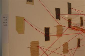 A lot of pages of different books hanging at two walls. single words are connected with a red thread