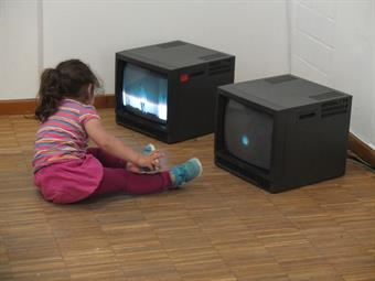 children in front of two TV´s