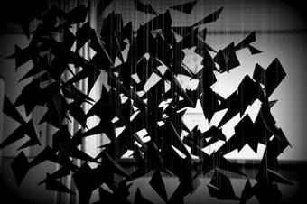 black birds folded out of paper. They hang from the top. Such a lot that they built a swarm.